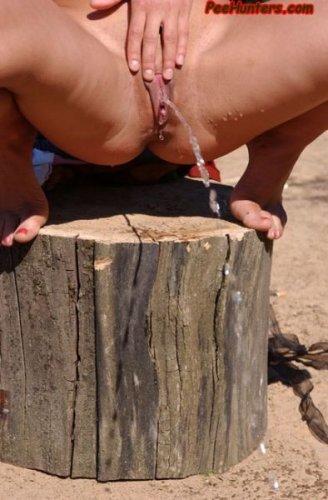 Горячая брюнетка на природе ссыт сидя, усевшись на пеньке